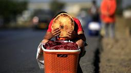 Issaac (8), memegang sepotong roti tradisional yang dijajakannya di tepi jalan raya di pinggiran Algiers, Aljazair, 13 Juni 2016. Selama bulan Ramadan, sejumlah anak membantu orangtuanya menjajakan roti di kawasan ini. (REUTERS/Zohra Bensemra)