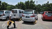 Sejumlah mobil hasil razia dan ban tergembok terparkir di IRTI Monas, Jakarta, Senin (13/3). Pada periode Januari-Febuari, Dishub menindak 6.437 kendaraan dengan sanksi ditilang. (Liputan6.com/Yoppy Renato)