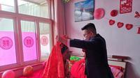 Zhang Long mengangkat kain merah penutup wajah sang mempelai wanita, Chen Xiao, saat pernikahan mereka pada 6 Februari 2020. (Xinhua)