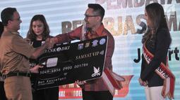 Gubernur DKI Jakarta Anies Baswedan secara simbolis menyerahkan kartu pembayaran Samsat Digital dan Pembayaran Non Tunai di Jakarta, Senin (26/3). Selain mempermudah, sistem ini juga untuk menghindari terjadinya pungli. (Merdeka.com/Iqbal Nugroho)