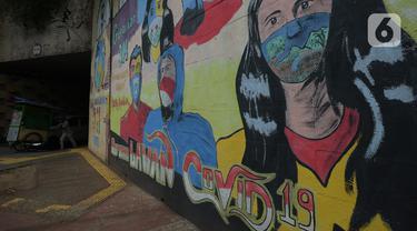 Pedagang melintas di depan mural anjuran kebiasan hidup baru dengan 3 M di Stasiun Cawang, Jakarta, Sabtu (26/12/2020). Pemerintah terus berupaya melakukan imbauan kepada warga untuk melaksanakan kebiasaan baru 3M guna memutus penyebaran virus corona (COVID-19). (merdeka.com/Imam Buhori)
