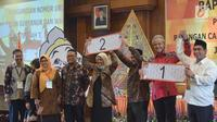 Pasangan calon gubernur Ganjar Pranowo dan Taj Yasin serta Pasangan calon gubernur  Sudirman Said dan Ida Fauziah menunjukkan nomor urut undian calon Gubernur dan Wakil Gubernur Jawa Tengah , Selasa (13/2) malam. (Liputan6.com/Gholib)