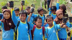 Pelajar menunjukkan tanaman mangrove saat kegiatan Pertamina Lestarikan Lingkungan di Hutan Mangrove Karangsong, Indramayu, Jumat (15/1). Kawasan tersebut merupakan Mangrove Center di Jabar yang memiliki lebih dari 15.000 bakau (Liputan6.com/Helmi Afandi)