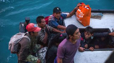 Penduduk Pulau Sebuku menunggu proses evakuasi sebelum menaiki kapal TNI Angkatan Laut dari rumah mereka yang terkena dampak tsunami di perairan Selat Sunda (28/12). (AP Photo/Fauzy Chaniago)