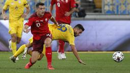 Gelandang Swiss, Granit Xhaka, berebut bola dengan penyerang Ukraina, Junior Moraes, pada laga Nations League di Stadion Arena Lviv, Jumat (4/9/2020) dini hari WIB. Ukraina menang 2-1 atas Swiss. (AFP/Anatolii Stepanov)