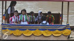 Sejumlah siswa SD menyeberangi sungai dengan perahu eretan untuk berangkat ke sekolah di Sungai Ciliwung, Jakarta, Senin, (4/1). Usai libur panjang para siswa kembali beraktivitas mengikuti tahun ajaran 2016-2017. (Liputan6.com/Gempur M Surya)
