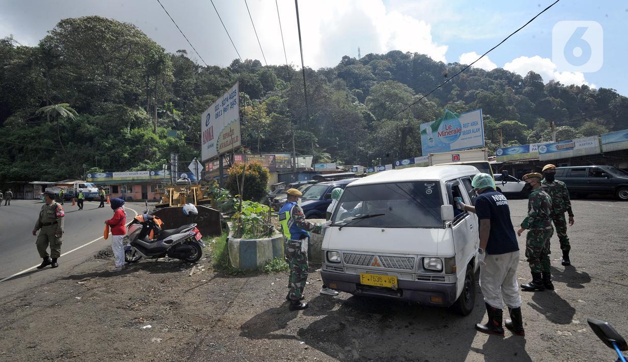 Petugas memeriksa kendaraan saat penyekatan arus lalu lintas di kawasan Ciloto, Cianjur, Jawa Barat, Jumat (17/4/2020). Pemkab Cianjur melakukan pengecekan suhu tubuh dan penyemprotan disinfektan di sejumlah titik keluar-masuk Cianjur untuk mencegah penyebaran COVID-19. (merdeka.com/Arie Basuki)