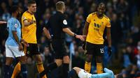 Wasit menghampiri pemain Wolverhampton Wanderers, Willy Boly (kanan) usai melanggar Bernardo Silva dalam pekan ke-22 Premier League di Stadion Etihad, Manchester, Senin (14/1). (AP Photo/Dave Thompson)