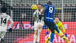 Striker Inter Milan, Romelu Lukaku melepaskan tendangan yang dihalangi bek Juventus, Leonardo Bonucci dalam laga lanjutan Liga Italia Serie A 2020/21 pekan ke-18 di San Siro Stadium, Minggu (17/1/2021). Inter Milan menang 2-0 atas Juventus. (AFP/Miguel Medina)