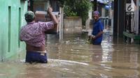 Warga melintasi banjir di kampung Arus Cawang, Jakarta Timur, Jumat (26/4). Ketinggan banjir kurang lebih satu meter terjadi akibat luapan kali Ciliwung dan intensitas curah hujan di kawasan Bogor Jawa Barat sangat tinggi sehingga aktivitas warga terhambat. (merdeka.com/Imam Buhori)