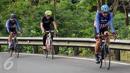 Pebalap sepeda, M Fadli (tengah) saat berlatih di jalan Raya Puncak Cianjur, Bogor, Kamis (23/2). Usai amputasi sebagian kaki kirinya, M Fadli menyatakan pensiun dari balap motor dan menekuni balap sepeda untuk difabel. (Liputan6.com/Helmi Fithriansyah)