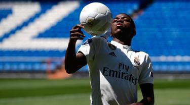 Penyerang baru Real Madrid, Vinicius Junior mengontrol bola dengan bahunya selama presentasi resmi dirinya di Stadion Santiago Bernabeu, Madrid (20/7). Vinicius sudah direkrut Madrid pada bursa transfer musim panas 2017. (AFP Photo/Pierre-Philippe Marcou)