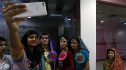 Sejumlah model berselfie di sela kegiatan lomba rias pengantin lokal di Karachi, Pakistan, 22 Maret 2016. Sejumlah wanita mengikuti lomba yang diadakan di sebuah pusat pembelajaan. (REUTERS / Akhtar Soomro)