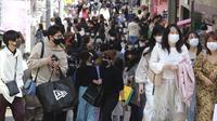 Orang-orang yang memakai masker wajah untuk melindungi dari penyebaran virus corona berjalan di sebuah jalan di Tokyo, Rabu (31/3/2021).  Ibukota Jepang mengonfirmasi lebih dari 410 kasus virus corona baru pada hari Rabu. (AP Photo/Koji Sasahara)