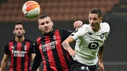 Penyerang AC Milan, Ante Rebic, berebut bola dengan bek Lille, Sven Botman, pada laga lanjutan Liga Europa 2020/2021 di San Siro, Jumat (6/11/2020) dini hari WIB. AC Milan kalah 0-3 oleh Lille. (AFP/Miguel Medina)