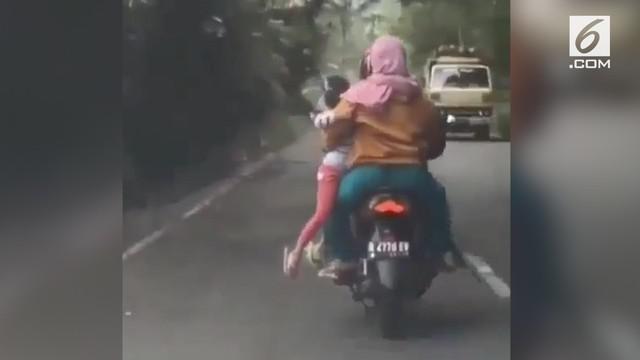 Emak-emak ini membonceng anaknya dengan cara digendong dari samping, sehingga si anak bergelantungan.