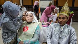 Pasangan pengantin dirias saat akan mengikuti nikah massal di Surabaya, Jawa Timur, Rabu (18/12/2019). Sebanyak 60 pasangan pengantin mengikuti nikah massal yang digelar Dinas Sosial Kota Surabaya. (JUNI KRISWANTO/AFP)