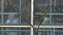 Anggota tim WHO mengenakan APD selama kunjungan lapangan ke Pusat Pengendalian dan Pencegahan Penyakit Hewan Hubei di Wuhan di provinsi Hubei, China tengah, Selasa (2/2/2021). Virus corona muncul pertama kali di provinsi Hubei, China, pada akhir tahun 2019. (AP Photo/ Ng Han Guan)