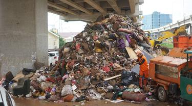 Petugas mengangkut sampah sisa banjir yang menumpuk di kawasan Cipinang Melayu, Jakarta, Senin (6/1/2020). Banjir yang menggenangi Jakarta dan sekitarnya sejak 1 Januari 2020 lalu menyisakan tumpukan sampah di sejumlah titik. (Liputan6.com/Immanuel Antonius)