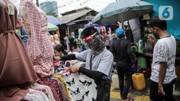 Pedagang menggunakan alat pelindung wajah (Face Shield) saat melayani pembeli di Kawasan Tanah Abang, Jakarta, Senin (18/5/2020). Penggunaan alat pelindung wajah itu sebagai upaya untuk melindungi diri saat berhubungan dengan pembeli dalam pecegahan penyebaran COVID-19. (Liputan6.com/Faizal Fanani)
