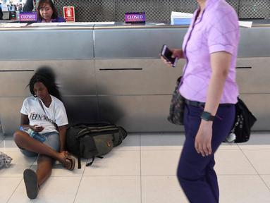 Penumpang beristirahat di area check-in di Bandara Internasional Suvarnabhumi di Bangkok (28/2). Puluhan penerbangan menuju Eropa dibatalkan setelah Pakistan menutup wilayah udaranya karena ketegangan dengan India meningkat. (AFP Photo/Lillian Suwnrumpha)