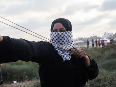 Wanita Palestina memakai ketapel untuk melemparkan batu ke arah pasukan Israel saat bentrok di Khan Yunis, Jalur Gaza, Jumat (13/9/2019). Warga berunjuk rasa dalam aksi damai Great March of Return di Jalur Gaza. (SAID KHATIB/AFP)
