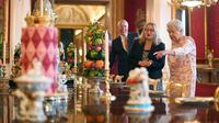Ratu Inggris Elizabeth II melihat penataan makanan penutup yang biasa dimakan Ratu Victoria sebagai bagian dari pameran di Istana Buckingham, London, Rabu (17/7/2019). Pameran yang dibuka pada 20 Juli ini menandai peringatan 200 tahun kelahiran Ratu Victoria. (Victoria Jones/POOL/AFP)