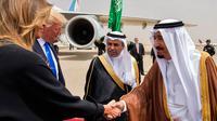 Melania Trump (kiri) berjabat tangan dengan Raja Arab Saudi Salman bin Abdulaziz al-Saud saat di Bandara Internasional Raja Khalid di Riyadh (20/5). (AFP/Saudi Royal Palace/Bandar Al-Jalou)