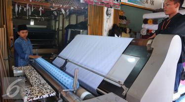 Pekerja tengah menggulung bahan di Pasar Cipadu, Tangerang, Selasa (30/8).Dirjen Industri Kimia, Tekstil, dan Aneka (IKTA) Kemenperin optimistis kinerja industri tekstil dan produk tekstil nasional akan gemilang. (Liputan6.com/Angga Yuniar)