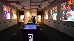 Orang-orang mengunjungi Museum Grammy pada hari pertama dibuka kembali setelah lebih dari setahun ditutup akibat COVID-19 di Los Angeles, Jumat (21/5/2021). Mulai 15 Juni, California akan mencabut sebagian besar pembatasan pandemi, termasuk jarak sosial dan penggunaan masker. (Frederic J. BROWN/AFP)