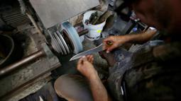 Seorang pria Palestina menajamkan pisau yang akan digunakan untuk menyembelih hewan kurban dalam perrayaan Idul Adha di sebuah lokakarya di Kota Gaza, 28 Juli 2020.  Idul Adha merupakan salah satu tanggal penting dalam kalender Islam. (AP Photo/Hatem Moussa)