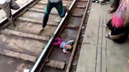 Gambar dari video pada 20 November 2018, bayi perempuan terjatuh dalam keadaan telentang di samping rel di stasiun kereta api di Mathura, Uttar Pradesh. Bayi satu tahun bernama Sahiba itu jatuh saat sebuah kereta melintas di atasnya. (NNIS / AFP)