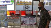 Calon penumpang melintas di depan agen tiket bus di Terminal Jatijajar, Depok, Jawa Barat, Senin (6/7/2020). Terminal tipe A tersebut kembali mengoperasikan layanan bus Antar Kota Antar Provinsi (AKAP) dengan menerapkan protokol kesehatan. (Liputan6.com/Herman Zakharia)