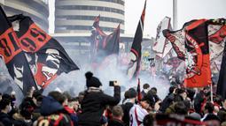 Para pendukung AC Milan mengibarkan bendera dan menyalakan flare di luar Stadion San Siro sebelum dimulainya laga lanjutan Liga Italia 2020/21 antara AC Milan melawan Inter Milan, Minggu (21/2/2021). AC Milan kalah 0-3 dari Inter Milan. (LaPresse via AP/Claudio Furlan)