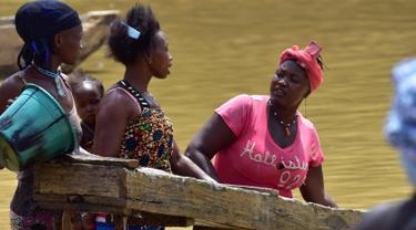 Para penambang emas wanita bekerja di sungai Pampana di dekat Mekeni, sebelah utara Sierra Leone (5/3). Melintasi tanah yang curam, ratusan pria dan wanita di sungai menyaring kerikil, memisahkan bintik-bintik emas dari lumpur. (AFP Photo/Issouf Sanogo)