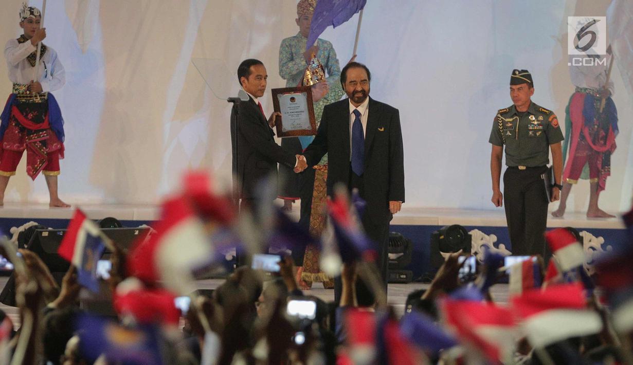 Ketum Partai Nasdem, Surya Paloh memberi piagam kepada Presiden Joko Widodo saat Rapat Kerja Nasional (Rakernas) IV Partai Nasdem di JIExpo Kemayoran, Jakarta Pusat, Rabu (15/11). (Liputan6.com/Faizal Fanani)