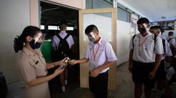 Guru dengan mengenakan pelindung wajah memberikan cairan pembersih tangan kepada siswa sebelum kelas di Samkhok School di Pathum Thani, Bangkok, Rabu (1/7/2020). Thailand telah memulai fase kelima relaksasi pembatasan covid-19 yang memungkinkan kembali dibukanya sekolah-sekolah. (AP/Sakchai Lalit)