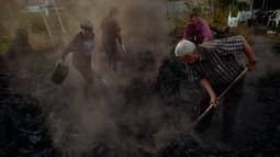 Para pekerja memadamkan api batang pohon sebagai bagian dari pembuatan arang tradisional di Viloria, Spanyol utara (11/9). Hanya segelintir warga yang dapat membuat arang tradisional dari kayu bakar. (AP Photo/Alvaro Barrientos)