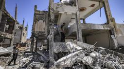 Pakar bahan peledak Hamas mencari proyektil yang tidak meledak dari reruntuhan bangunan setelah konflik Mei 2021 dengan Israel di Kota Gaza, Sabtu (5/6/2021). Perang 11 hari antara Hamas dan Israel menewaskan 254 orang Palestina dan 12 orang Israel. (MAHMUD HAMS/AFP)