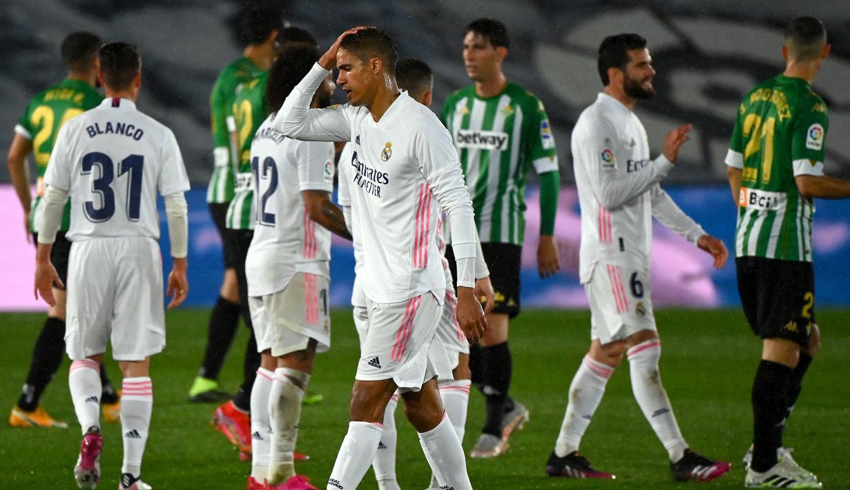 Ekspresi kecewa bek Real Madrid, Raphael Varane (tengah) usai ditahan imbang 0-0 Real Betis dalam laga lanjutan Liga Spanyol 2020/2021 pekan ke-33 di Alfredo Di Stefano Stadium, Madrid, Sabtu (24/4/2021). (AFP/Gabriel Bouys)