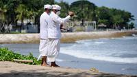 Umat Hindu berdoa saat upacara Melasti menjelang Hari Raya Nyepi Tahun Baru Saka 1943 di Pantai Kuta, Bali (11/3/2021).  Hari Raya Nyepi tahun ini jatuh pada tanggal 14 Maret 2021. (AFP/Sonny Tumbelaka)