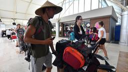 Wisatawan antre memasuki terminal keberangkatan Bandara Lombok Praya di pulau Lombok, NTB, Senin (6/8). BNPB melaporkan Bandara Lombok Praya pada pagi ini menjalani aktivitas seperti biasa setelah gempa dahsyat berkekuatan 7,0 SR. (AFP/Adek BERRY)