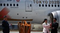 Presiden Olimpiade Tokyo 2020, Yoshiro Mori, menyaksikan dua atlet peraih tiga kali medali emas olimpiade Tadahiro Nomura dan Saori Yoshida menyalakan obor Olimpiade saat tiba dari Yunani di Pangkalan Udara Matsushima, Jepang, Jumat (20/3). (AFP/Philip Fong)