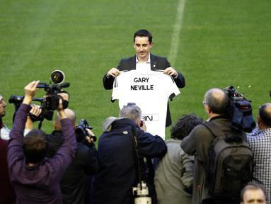Mantan Pemain Manchester United, Gary Neville berfoto dengan Jersey Valencia bertuliskan namanya di Stadion Mestalla, Kamis (3/12/2015). Gary didaulat sebagai pelatih baru Valencia. (AFP Photo/Jose Jordan)