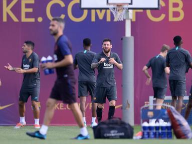 Penyerang Barcelona, Lionel Messi (tengah) melakukan pemanasan saat mengikuti sesi latihan tim di Joan Gamper Sports City, Spanyol (16/9/2019). Barcelona akan menghadapi wakil Jerman, Borussia Dortmund pada grup F Liga Champions di Signal Iduna Park. (AFP Photo/Pau Barrena)