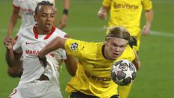Striker Borussia Dortmund, Erling Haaland, berebut bola dengan pemain Sevilla, Jules Kounde, pada laga Liga Champions di Stadion Ramon Sanchez Pizjuan, Kamis (18/2/2021). Dortmund menang dengan skor 2-3. (AP/Angel Fernandez)