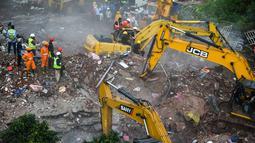 Petugas penyelamat mencari korban di reruntuhan gedung apartemen yang runtuh di Mahad, India (25/8/2020). Sedikitnya 50 orang terjebak dalam semalam di dalam apartemen yang runtuh tersebut. (AFP Photo/Punit Paranjpe)