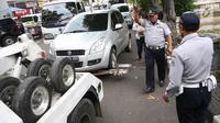 Mobil Dinas Perhubungan menderek kendaraan yang terjaring parkir liar di kawasan Pasar Baru, Jakarta, Kamis (14/12). Meskipun sering ditertibkan, namun masih banyak pengendara yang nekat parkir sembarangan. (Liputan6.com/Immanuel Antonius)