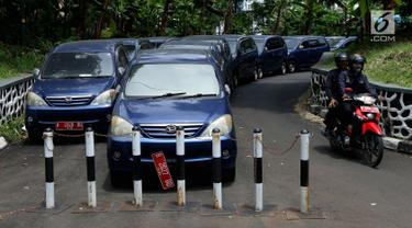 Pengendara motor melintasi deretan mobil dinas yang terparkir di area belakang Gedung DPR/MPR, Jakarta, Selasa (5/12).  Mobil-mobil berplat merah tersebut dibiarkan mangkrak hingga berkarat lantaran menunggu proses lelang. (Liputan6.com/Johan Tallo)