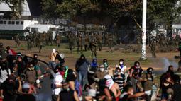 Polisi berlari ke arah demonstran antipemerintah saat protes di Santiago, Chile, Jumat (27/12/2019). Sebagian besar dari daftar panjang tuntutan demonstran Chile berfokus pada ketidaksetaraan. (AP Photo/Fernando Llano)